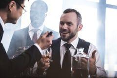 Ομάδα Multiethnic επιχειρηματιών που καπνίζουν και που πίνουν το ουίσκυ στο εσωτερικό Στοκ Εικόνα