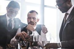 Ομάδα Multiethnic επιχειρηματιών που καπνίζουν και που πίνουν το ουίσκυ στο εσωτερικό Στοκ Εικόνες