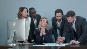 Ομάδα multiethnic διαφορετικών νέων επιχειρηματιών σε μια συνεδρίαση που στέκεται γύρω από έναν πίνακα με τις σοβαρές εκφράσεις φιλμ μικρού μήκους