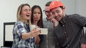 Ομάδα selfie που πυροβολείται των συναδέλφων που έχουν τη διασκέδαση στο γραφείο τους φιλμ μικρού μήκους