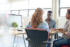 Ομάδα Unposed δημιουργικών επιχειρηματιών σε ένα ανοικτό 'brainstorming' γραφείων έννοιας το επόμενο πρόγραμμά τους Στοκ Φωτογραφία