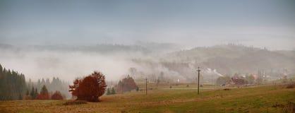 Ομίχλη φθινοπώρου στο ορεινό χωριό Νεφελώδες βροχερό misty φθινόπωρο Στοκ εικόνα με δικαίωμα ελεύθερης χρήσης