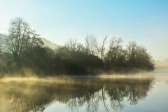 Ομίχλη και υδρονέφωση χειμερινού πρωινού στη λίμνη ή τον ποταμό Στοκ Φωτογραφίες