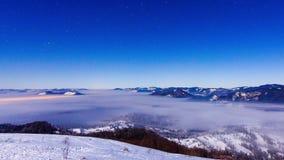 Ομίχλη που κινείται πέρα από το βουνό το χειμώνα με έναν αστεροειδή ουρανό φιλμ μικρού μήκους