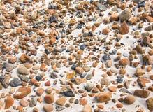 Ομαλές στρογγυλές πέτρες χαλικιών στην παραλία άμμου backgound Στοκ Φωτογραφίες