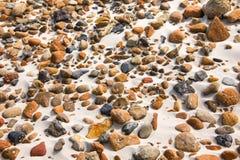 Ομαλές στρογγυλές πέτρες χαλικιών στην παραλία άμμου backgound Στοκ Εικόνες