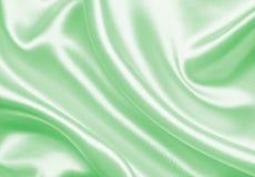 Ομαλό κομψό πράσινο μετάξι ή σατέν ως υπόβαθρο Στοκ εικόνα με δικαίωμα ελεύθερης χρήσης