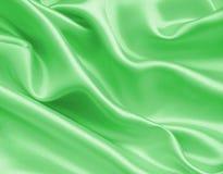 Ομαλό κομψό πράσινο μετάξι ή σατέν ως υπόβαθρο Στοκ Εικόνες