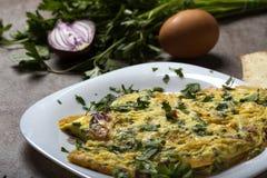 Ομελέτα που γίνεται από τα αυγά, το μπέϊκον, το τυρί και το κρεμμύδι στοκ εικόνες