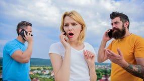 Ομιλία με τους φίλους Φίλοι που χρησιμοποιούν το τηλέφωνο 3 νέοι στο pho στοκ εικόνα
