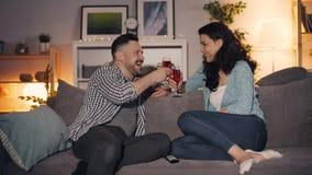Ομιλούντα clinking γυαλιά ανδρών και γυναικών που πίνουν τη συνεδρίαση κρασιού στον καναπέ στο σπίτι απόθεμα βίντεο