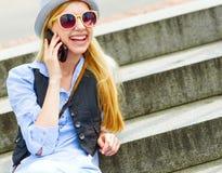 Ομιλούν τηλέφωνο κυττάρων κοριτσιών Hipster καθμένος στα σκαλοπάτια Στοκ εικόνες με δικαίωμα ελεύθερης χρήσης