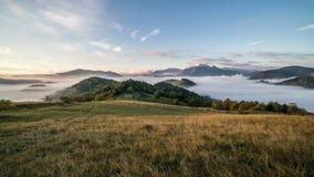 Ομιχλώδης ανατολή πρωινού με τα σύννεφα που κινούνται πέρα από την όμορφη χώρα στο χρονικό σφάλμα βουνών φιλμ μικρού μήκους