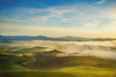 Ομιχλώδες πανόραμα Volterra, κυλώντας λόφοι και πράσινοι τομείς στο sunse στοκ εικόνα