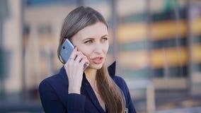 Ομιλούν τηλέφωνο επιχειρησιακών γυναικών Βέβαια νέα γυναίκα εργαζόμενος που έχει τη τηλεφωνική συνομιλία που στέκεται στο κτίριο  φιλμ μικρού μήκους