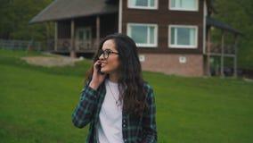 Ομιλούν τηλέφωνο κοριτσιών στο υπόβαθρο του σπιτιού απόθεμα βίντεο