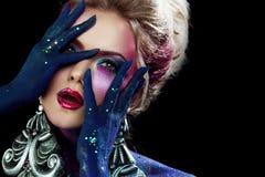 Ομορφιά γοητείας στον κλονισμό Το νέο ελκυστικό ξανθό κορίτσι στη φωτεινή τέχνη -τέχνη-makeup, τα χέρια ένα κεφάλι Στοκ Εικόνες