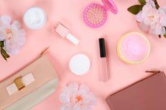 Ομορφιά που τίθεται με τα διακοσμητικά καλλυντικά στιλβωτική ουσία, βούρτσες και τσάντα καρφιών στο ρόδινο πρότυπο άποψης υποβάθρ στοκ φωτογραφία