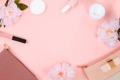Ομορφιά που τίθεται με τα διακοσμητικά καλλυντικά στιλβωτική ουσία, βούρτσες και τσάντα καρφιών στο ρόδινο πρότυπο άποψης υποβάθρ στοκ φωτογραφίες