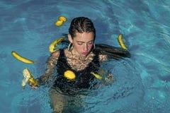 Ομορφιά προσώπου γυναικών τα όμορφα νέα κορίτσια κολυμπούν με την μπανάνα και το λεμόνι στη λίμνη Στοκ Φωτογραφίες
