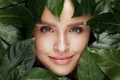 ομορφιά φυσική Όμορφο πρόσωπο γυναικών στα πράσινα φύλλα Στοκ εικόνα με δικαίωμα ελεύθερης χρήσης