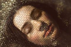 Ομορφιά ύπνου με τη σκοτεινή τρίχα κάτω από το χρυσό πλέγμα Στοκ Φωτογραφία