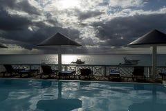 Ομπρέλα θαλάσσης που απεικονίζει στη λίμνη ξενοδοχείων στο ηλιοβασίλεμα πέρα από τη θάλασσα Στοκ Εικόνα
