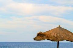Ομπρέλα και θάλασσα φύλλων φοινικών Ειρηνικό τοπίο του τροπικού θερέτρου νησιών Στοκ εικόνα με δικαίωμα ελεύθερης χρήσης
