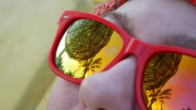 Ομπρέλα και φοίνικας παραλιών που απεικονίζονται στην αντανάκλαση των γυαλιών ηλίου απόθεμα βίντεο