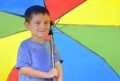 Ομπρέλα ουράνιων τόξων εκμετάλλευσης αγοριών Στοκ Φωτογραφία