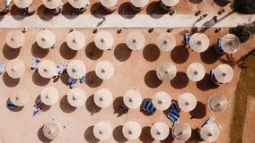 Ομπρέλες, καρέκλες γεφυρών και τουρίστες που χαλαρώνουν στην παραλία φιλμ μικρού μήκους