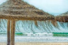 Ομπρέλες παραλιών αχύρου στο τυρκουάζ υπόβαθρο μπλε ουρανού κυμάτων θάλασσας παραλιών άμμου φωτεινό φως του ήλιου Ταξίδι Wanderlu Στοκ φωτογραφία με δικαίωμα ελεύθερης χρήσης