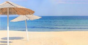 Ομπρέλες παραλιών και καθαρή άμμος ενάντια στοκ φωτογραφίες