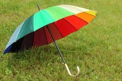 Ομπρέλα ουράνιων τόξων στο χορτοτάπητα Στοκ εικόνα με δικαίωμα ελεύθερης χρήσης