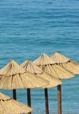 Ομπρέλες αχύρου σε μια παραλία με το τυρκουάζ νερό Στοκ φωτογραφίες με δικαίωμα ελεύθερης χρήσης