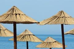 Ομπρέλες αχύρου στην παραλία με το τυρκουάζ νερό Στοκ φωτογραφίες με δικαίωμα ελεύθερης χρήσης