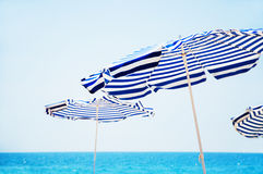 Ομπρέλες παραλιών, μπλε θάλασσα και ουρανός Στοκ Εικόνες