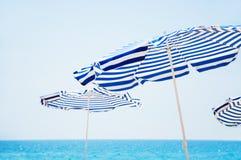 Ομπρέλες παραλιών, μπλε θάλασσα στο υπόβαθρο Στοκ εικόνα με δικαίωμα ελεύθερης χρήσης