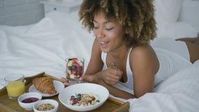 Ονειρεμένος γυναίκα που έχει το γλυκό γεύμα στο κρεβάτι απόθεμα βίντεο