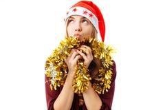 Ονειρεμένος γυναίκα σε ένα καπέλο και ένα φόρεμα santa, και με tinsel, σε ένα W στοκ φωτογραφία
