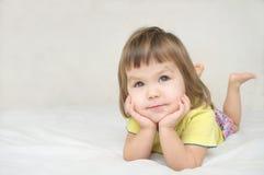 Ονειρεμένος κορίτσι που βρίσκεται στο χαμόγελο κρεβατιών ευτυχές Στοκ εικόνες με δικαίωμα ελεύθερης χρήσης