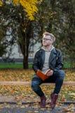 Ονειρεμένος τον ευτυχή τύπο στα περιστασιακά ενδύματα διαβάστε το βιβλίο και κάθεται σε έναν πάγκο πάρκων στοκ φωτογραφία με δικαίωμα ελεύθερης χρήσης