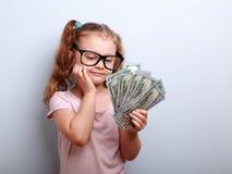 Ονειρεμένος το χαριτωμένο παιδί κορίτσι που κοιτάζει στα χρήματα και που σκέφτεται πώς μπορεί να ξοδεψει στοκ εικόνες
