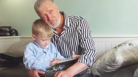 Ονειροπόλα αγκαλιάσματα grandpa που παίζουν στην ταμπλέτα ενός εγγονού απόθεμα βίντεο