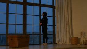 Ονειροπόλος νέα ασιατική γυναίκα που φαίνεται έξω το παράθυρο απόθεμα βίντεο