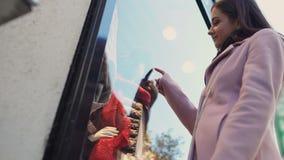 Ονειροπόλος νέα γυναίκα που εξετάζει τα ενδύματα σχεδιαστών στην προθήκη, βιομηχανία κλωστοϋφαντουργίας απόθεμα βίντεο