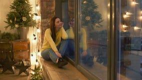 Ονειροπόλος όμορφη γυναίκα που φαίνεται έξω το παράθυρο τη νύχτα απόθεμα βίντεο