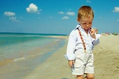 Ονειροπόλο αγοράκι που περπατά την παραλία θάλασσας Στοκ Εικόνες