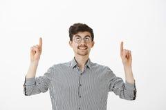 Ονειροπόλο όμορφο συνηθισμένο άτομο στα στρογγυλά γυαλιά, που χαμογελούν περίεργα ανατρέχοντας και δείχνοντας με τους αντίχειρες Στοκ φωτογραφίες με δικαίωμα ελεύθερης χρήσης