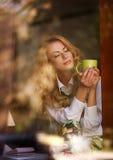 Ονειροπόλος γυναίκα με ένα φλιτζάνι του καφέ στον καφέ, που απολαμβάνει το άρωμα Στοκ Φωτογραφίες